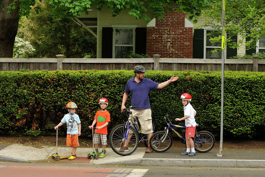 Father Eric Conte instructs his children, Will, left, Logan, center, and Baxter, to wait for traffic before crossing the street during their ride along Riverside Avenue in the Riverside section of Greenwich, Conn., on Sunday, May 18, 2014. Photo: Jason Rearick / Stamford Advocate