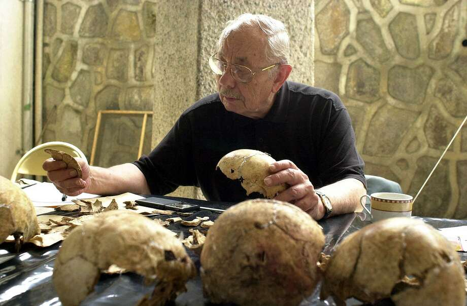 "American anthropologist Clyde Snow unites parts of a skull in San Salvador, El Salvador. ""Bones don't forget,"" Mr. Snow once told the Associated Press. Photo: Victor Ruiz C, Associated Press"