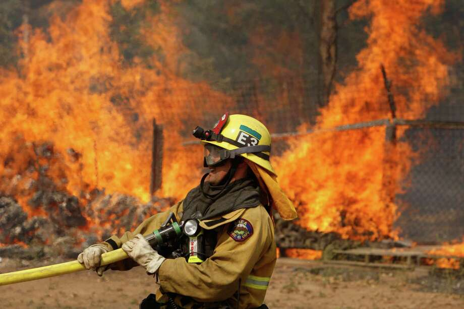 A firefighter pulls a hose in position while battling the Cocos fire on May 15 in San Marcos, Calif. Agencies throughout the state are scrambling to prepare for what is expected to be a dangerous year of wildfires. Photo: David McNew, Stringer / David McNew