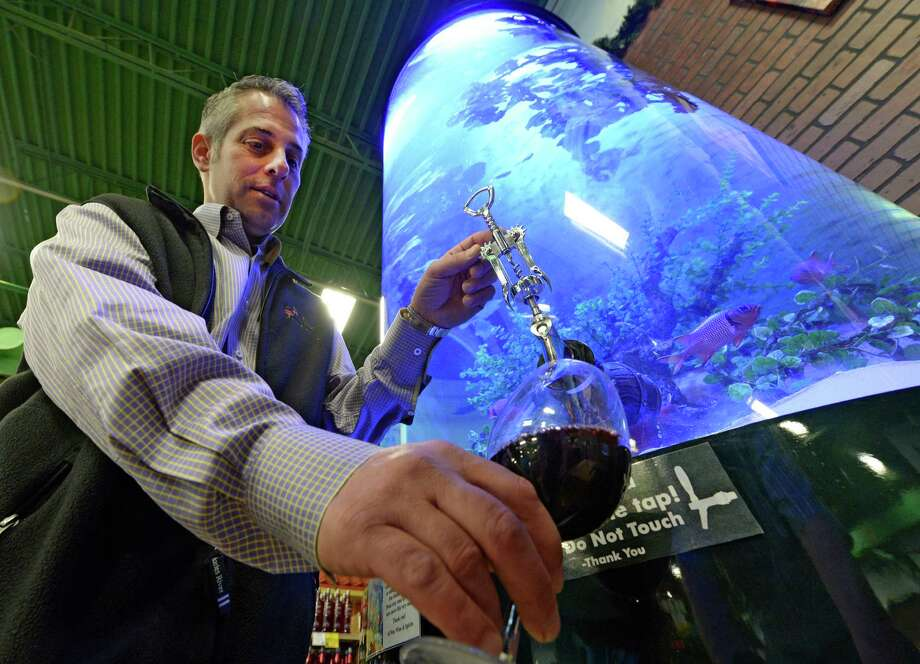 "All Star Wine & Spirits owner Craig Allen draws some wine from a specially designed spigot in the large fish tank Thursday, May 8, 2014, installed in his store by ""Tanked"" reality show members in Latham, N.Y.   Allen is starting fresh and introducing a new set of fish into the tank slowly. (Skip Dickstein / Times Union) Photo: SKIP DICKSTEIN / 00026818A"