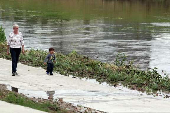 Sally Lehr and her grandson, 2 year-old Matteo Salazar, walk along Braes Bayou in the community of Idylwood in Houston's east end last Tuesday.