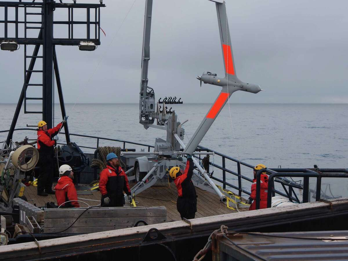 A crew works with an Insitu ScanEagle unmanned aerial vehicle during a test by ConocoPhillips last year in Alaska's Chukchi Sea.