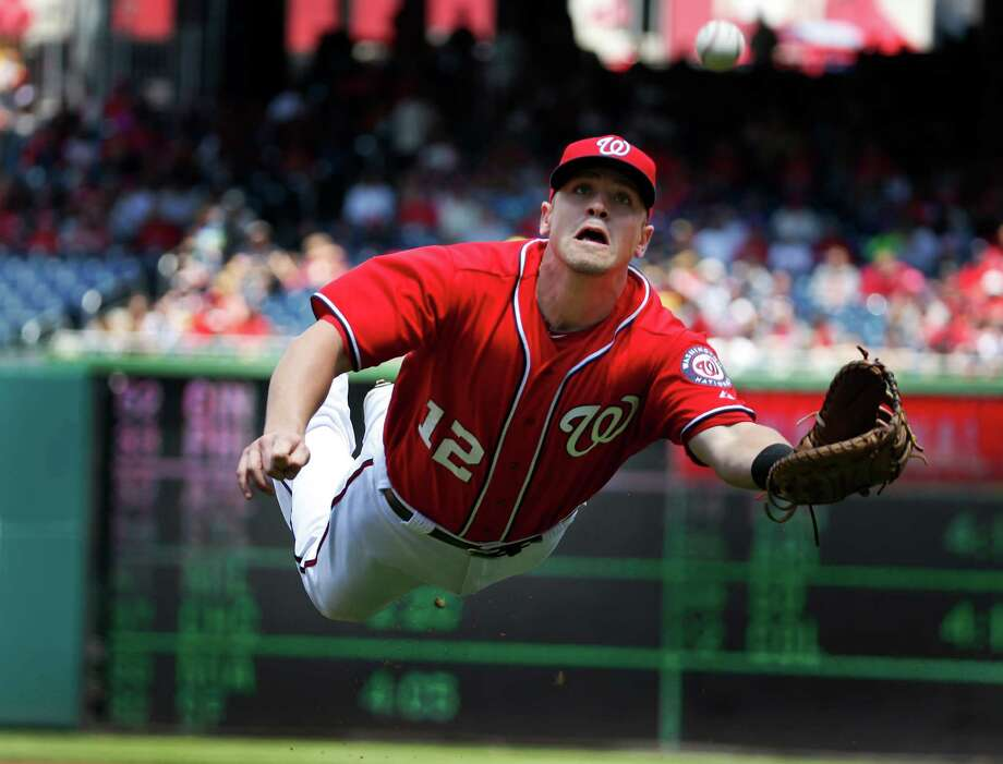 Washington Nationals first baseman Tyler Moore makes a diving catch for the out on a foul ball hit by New York Mets' Eric Young Jr. during the first inning of a baseball game at Nationals Park Sunday, May 18, 2014, in Washington. (AP Photo/Alex Brandon) ORG XMIT: NAT102 Photo: Alex Brandon / AP