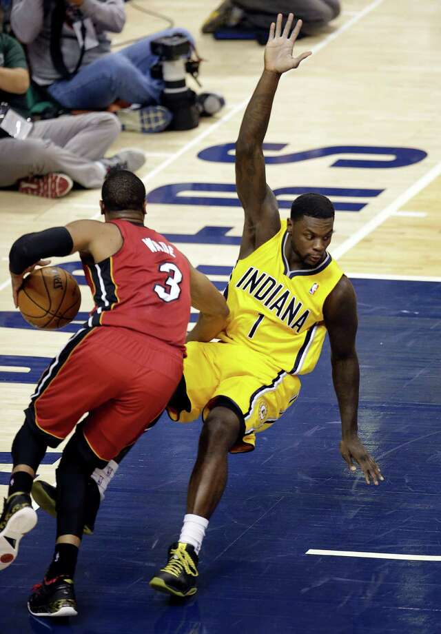 Pacers guard Lance Stephenson, right, draws a charge on the Heat's Dwyane Wade during the second half Sunday. Photo: AJ Mast, FRE / FR123854 AP