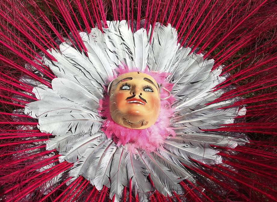 """A mask with Caucasian features rests in a feathered headdress belonging to a Mexican-American """"huehue"""" dancer who performed for members of his community in Brooklyn's Sunset Park, Sunday, May 18, 2014, in New York. """"Huehue"""" dancers, Mexicans and indigenous Indians from the area, satirize European landowners who colonized the area of Southeast Central Mexico several hundred years ago. Mexican-American Immigrants who perform the dance in New York dance to keep Mexican cultural traditions alive. (AP Photo/Kathy Willens) Photo: Kathy Willens, Associated Press"""