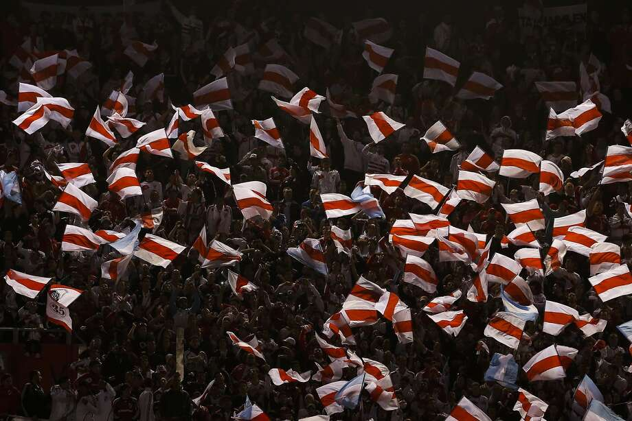 Fans wave River Plate flags during an Argentine league soccer match against Quilmes in Buenos Aires, Argentina, Sunday, May 18, 2014. River Plate won 5-0 to win the Argentine soccer league championship. (AP Photo/Victor R. Caivano) Photo: Victor R. Caivano, Associated Press
