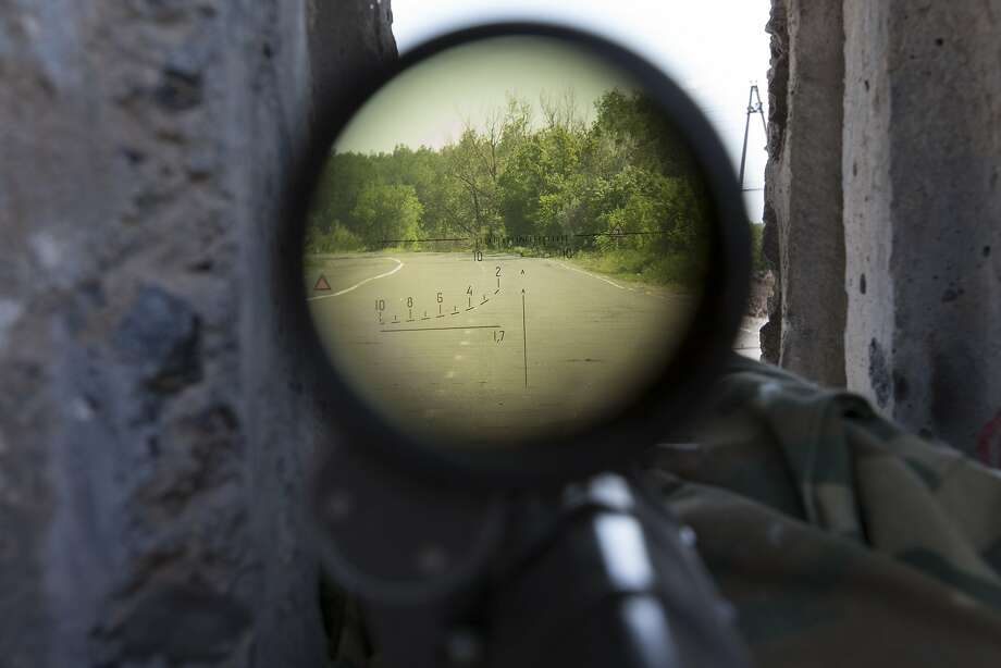 A view through a sniper's rifle from a pro-Russian checkpoint blocking the major highway which links Kharkiv, outside  Slovyansk, eastern Ukraine, Sunday, May 18, 2014. Lawmakers and officials from eastern Ukraine on Saturday poured criticism on the fledging central government, accusing it of ignoring legitimate grievances of the regions which have been overrun by pro-Russia militia fighting for independence.(AP Photo/Alexander Zemlianichenko) Photo: Alexander Zemlianichenko, Associated Press
