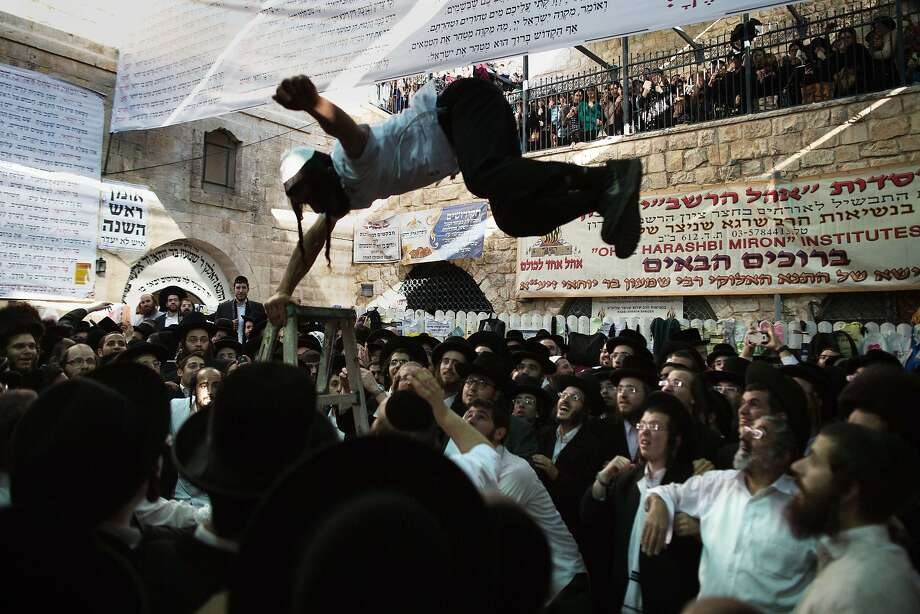 TOPSHOTS Ultra-Orthodox Jews dance at the grave site of Rabbi Shimon Bar Yochai in the northern Israeli village of Meron on May 18, 2014, at the start of the day-long holiday of Lag Baomer that commemorates the Jewish scholar's death. Thousands of religious Jews light large bonfires all night long and visit the shrine of Bar Yochai, one of the most prominent sages in Jewish history, during the holiday. AFP PHOTO/MENAHEM KAHANAMENAHEM KAHANA/AFP/Getty Images Photo: Menahem Kahana, AFP/Getty Images