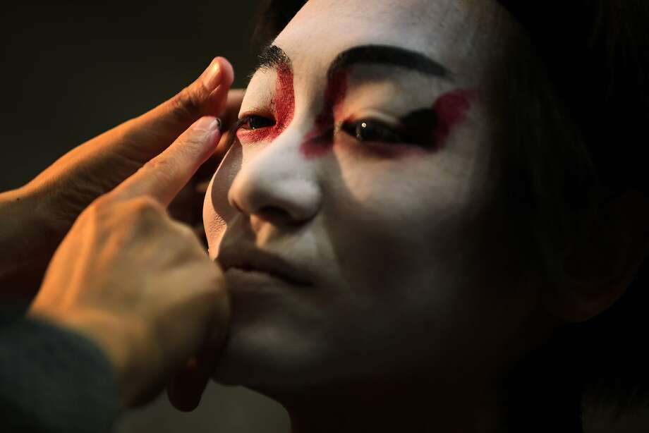 "A professional artisan of kabuki makeup paints a man's face with a pattern of makeup called ""Kumadori"" at an art event in Tokyo, Sunday, May 18, 2014. Red and black cosmetics are painted on the performers according to their role of play in kabuki story. (AP Photo/Eugene Hoshiko) Photo: Eugene Hoshiko, Associated Press"