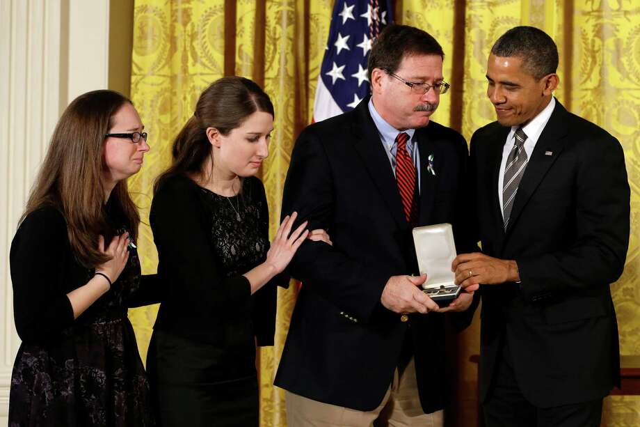 President Barack Obama presents a 2012 Citizens Medal to the family of Sandy Hook Elementary School school psychologist Mary Sherlach, including her daughter, Katy, second from left, in February 2013 at the White House in Washington. Photo: Jacquelyn Martin, Associated Press/Jacquelyn Marti / Associated Press