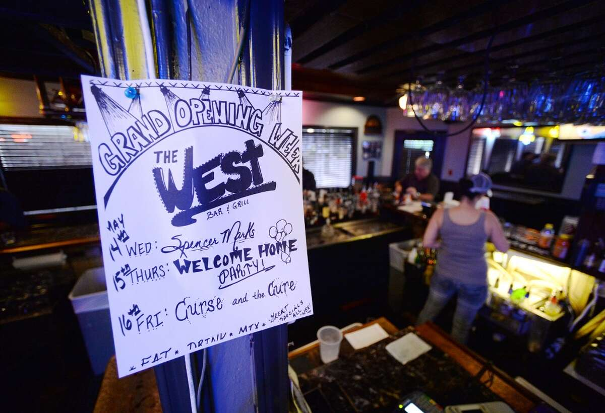 A sign near the bar announces the scheduled bands for The West's reopening in May. The newly reopened The West Bar and Grill on Calder Avenue is the CAT5 Bar of the Week for April 15, 2014. Photo taken Tuesday, 5/6/14 Jake Daniels/@JakeD_in_SETX
