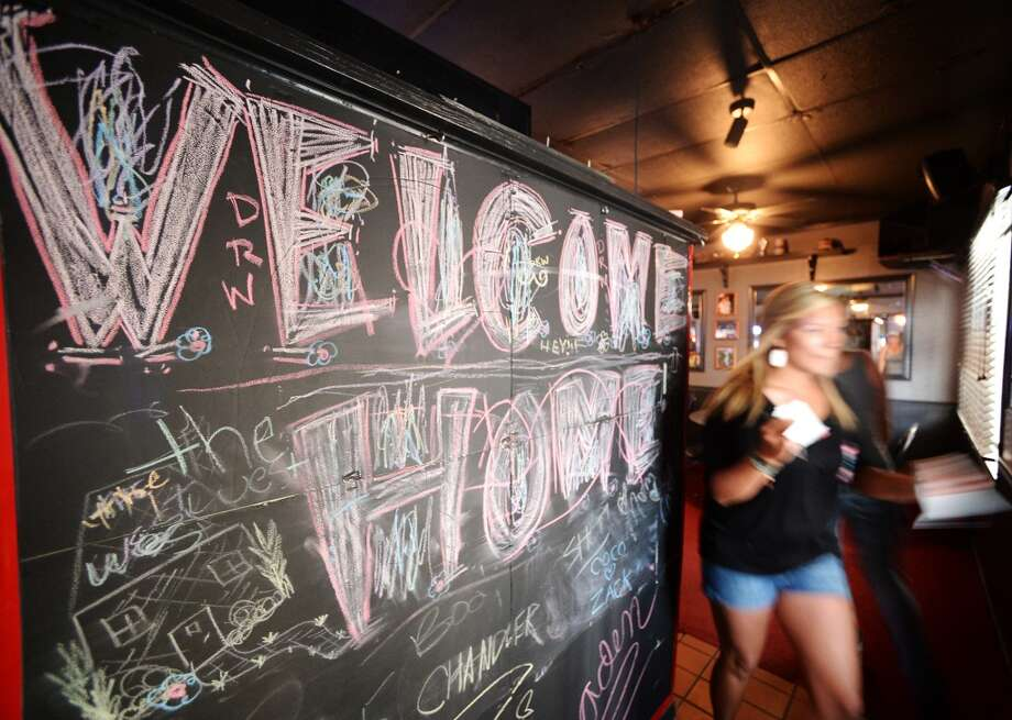 A woman walks by the chalkboard that greets newcomers to The West on Tuesday afternoon. The newly reopened The West Bar and Grill on Calder Avenue is the CAT5 Bar of the Week for April 15, 2014. Photo taken Tuesday, 5/6/14 Jake Daniels/@JakeD_in_SETX