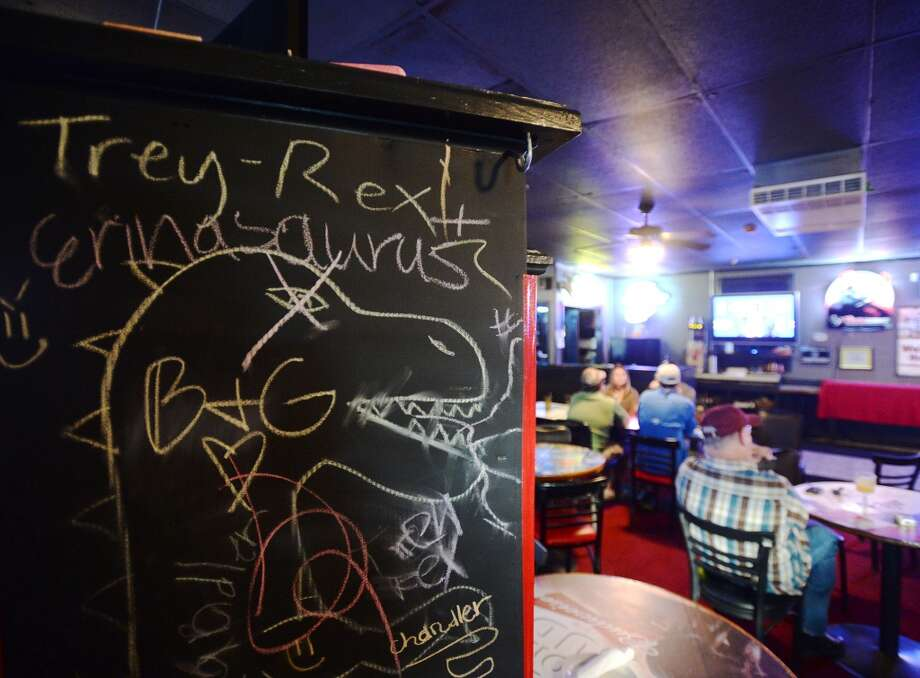 One face of the three-sided chalkboard near the front door of The West is decorated with a dinosaur and scribbles Tuesday afternoon. The newly reopened The West Bar and Grill on Calder Avenue is the CAT5 Bar of the Week for April 15, 2014. Photo taken Tuesday, 5/6/14 Jake Daniels/@JakeD_in_SETX