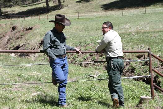 Otero cattle rancher association president Gary Stone talks to Lincoln National Forest District Ranger James Duran in Weed, New Mexico, Thursday, May 15, 2014. The Otero County Cattleman's Association is pitted against the National Forest Service over a fence intended to protect wildlife that the agency installed around a small creek where the ranchers' cattle drink water. Photo: Juan Carlos Llorca, AP / AP