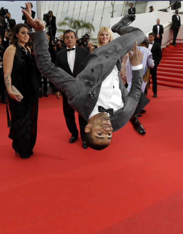 An unidentified person performs a stunt for photographers before the screening of Foxcatcher at the 67th international film festival, Cannes, southern France, Monday, May 19, 2014.  Photo: Thibault Camus, Associated Press