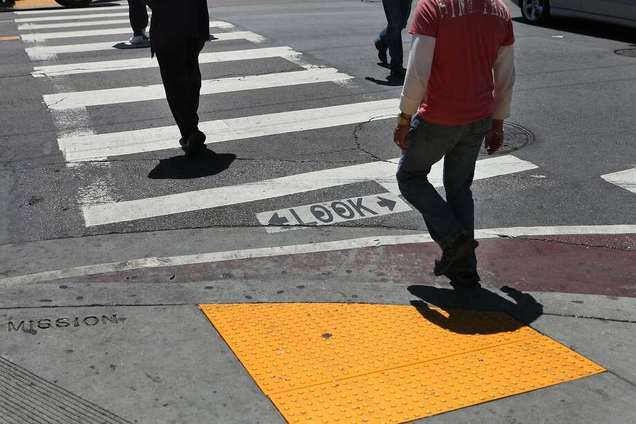 People cross Mission at Sixth Street in SoMa, where the intersection curbs have been extended to improve pedestrian safety. Photo: Deborah Svoboda, The Chronicle