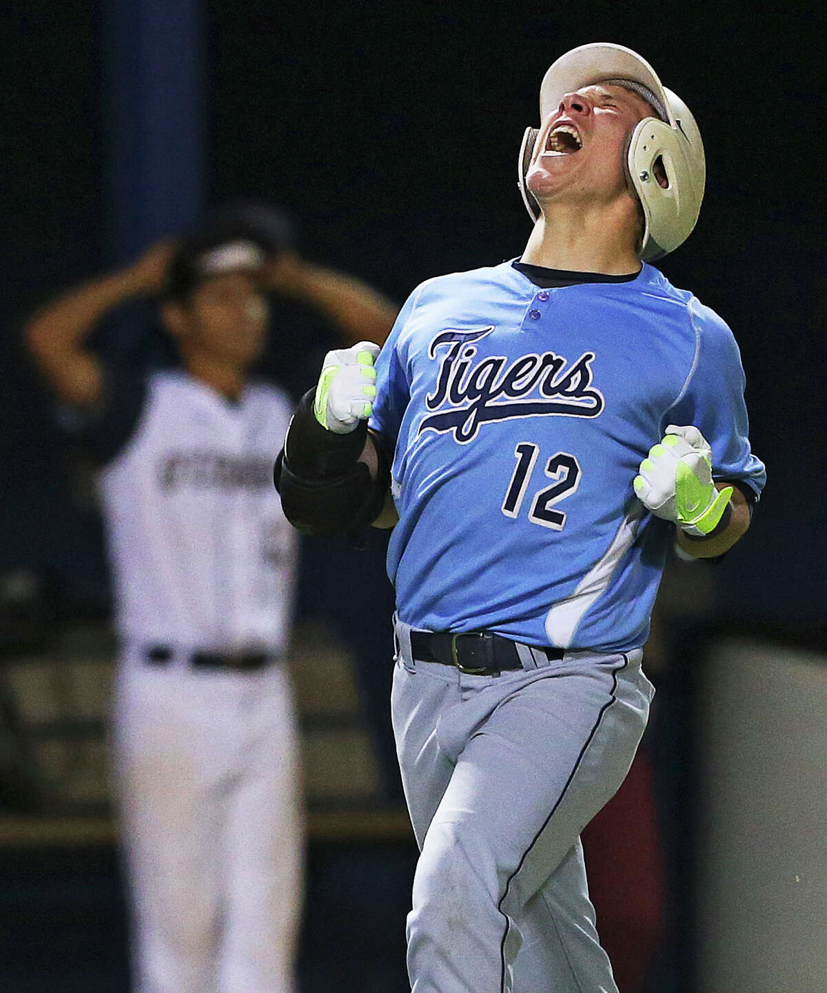 Tiger slugger Trace Bucey rounds third base celebrating after crushing a two run homer to right field late in the game as O'Connor plays Carroll in game 1 of the 5A regional quarterfinal match at SAISD Spring Sports Complex on May 15, 2014.