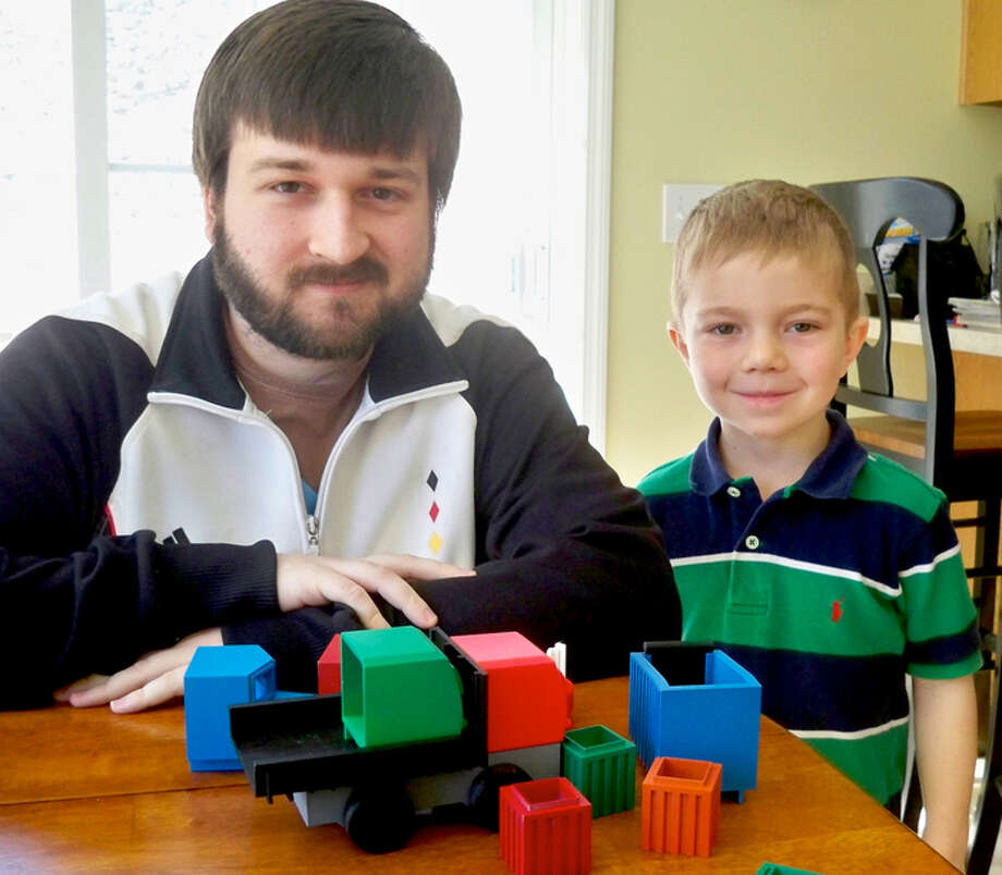 Newtown resident Luke Barber, along with neighborhood toy tester Connor Monaghan, shows a protoype version of the EcoTruck toy he hopes to produce locally using environmentally friendly and sustainable plastics. Photo: Contributed Photo / The News-Times Contributed