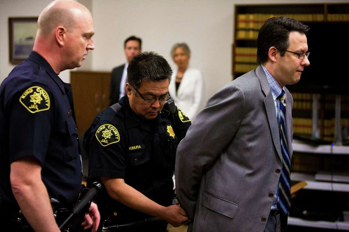 Former Seattle lawyer Danford Grant, right, is placed in handcuffs after being sentenced to 25 years in prison for raping multiple masseuses in the Seattle area Monday, May 19, 2014, in Seattle. The sentence - exceptionally high according to the state's sentencing recommendations for the crimes - had been agreed to ahead of the day's hearing.