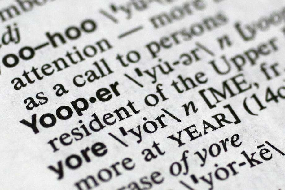 In this May 15, 2014 photo, ?Yooper,? one of the 150 new words appearing in Merriam-Webster's Collegiate Dictionary and the company's free online database appears on page 1454 of the printed edition of the dictionary in New York. The term refers to native or longtime residents of the Michigan's Lake Superior region known for a distinctive manner of speaking and its Scandinavian roots. Many of the other new words and terms stem from digital life and social media; spoiler alert; hashtag; selfie and tweep, while others are food driven, including pho and turducken, a boneless chicken stuffed with a boneless duck stuffed with a boneless turkey. (AP Photo/Mark Lennihan) Photo: Mark Lennihan, Associated Press