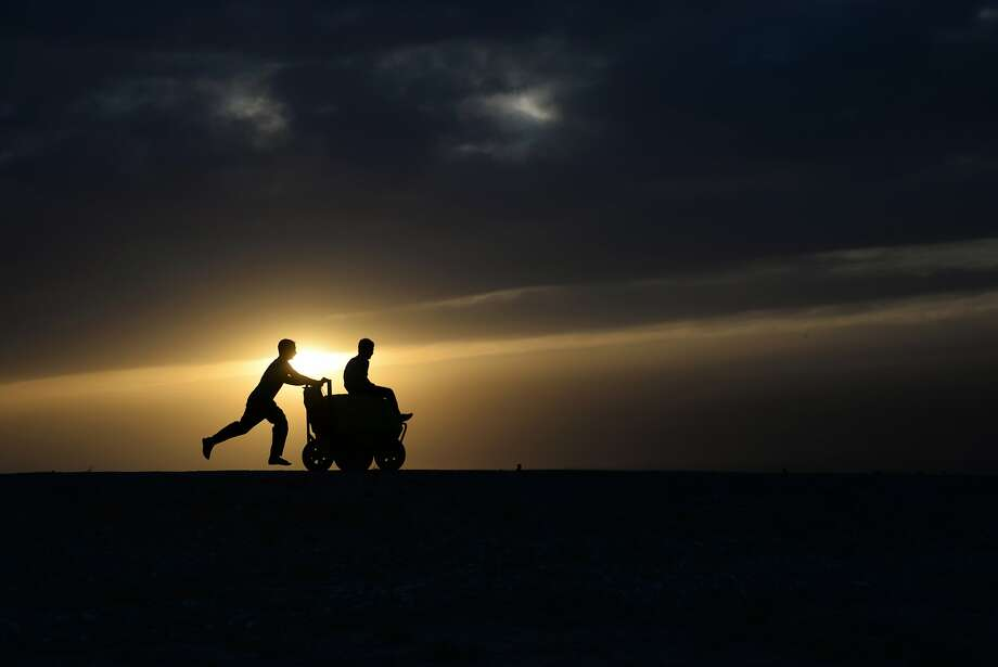 A boy gives his buddy a rideon an ice cream cart at sunset outside Mazar-i-Sharif, Afghanistan. Photo: Farshad Usyan, AFP/Getty Images