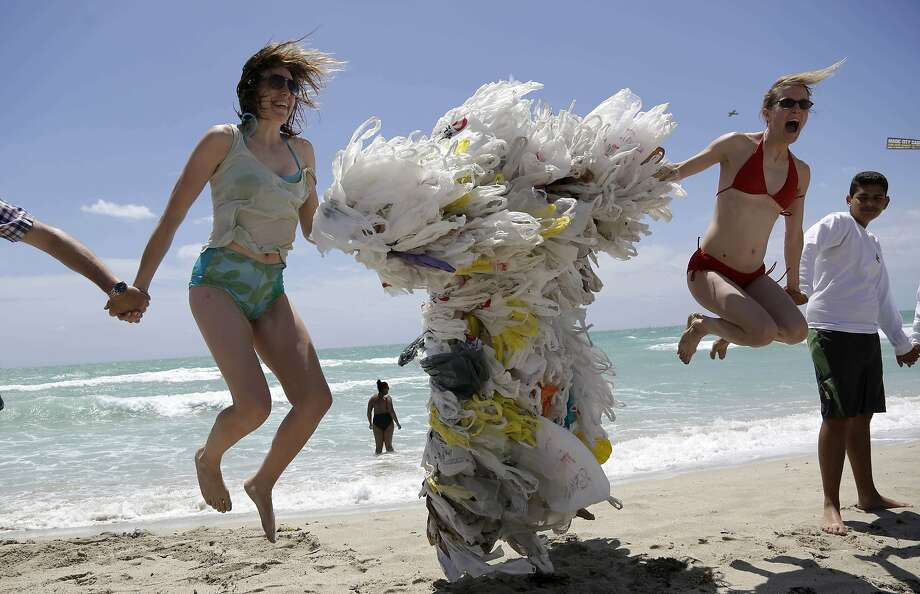 Dune baggies:Rachel Bennett (left) and Tiffany Threadgould leap into the air as a friend takes their photograph during the Hands   across the Sand protest in Miami Beach. Between them, covered in plastic bags, is Steve Vincenti. The purpose of   the event was to raise awareness of the need to end dependence on fossil fuels and transition to clean   energy. Photo: Lynne Sladky, Associated Press
