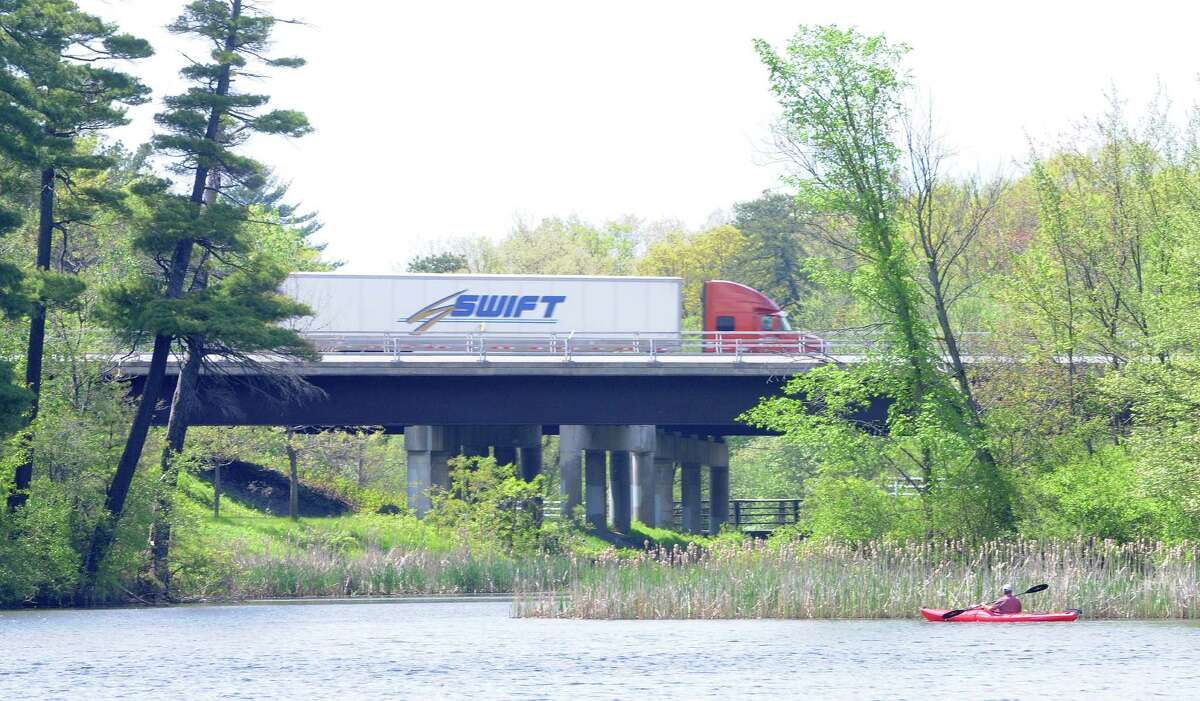 A kayaker paddles along the shoreline at Rensselaer Lake as traffic zips by on Interstate 87 on Monday, May 19, 2014, in Albany, N.Y. (Paul Buckowski / Times Union)