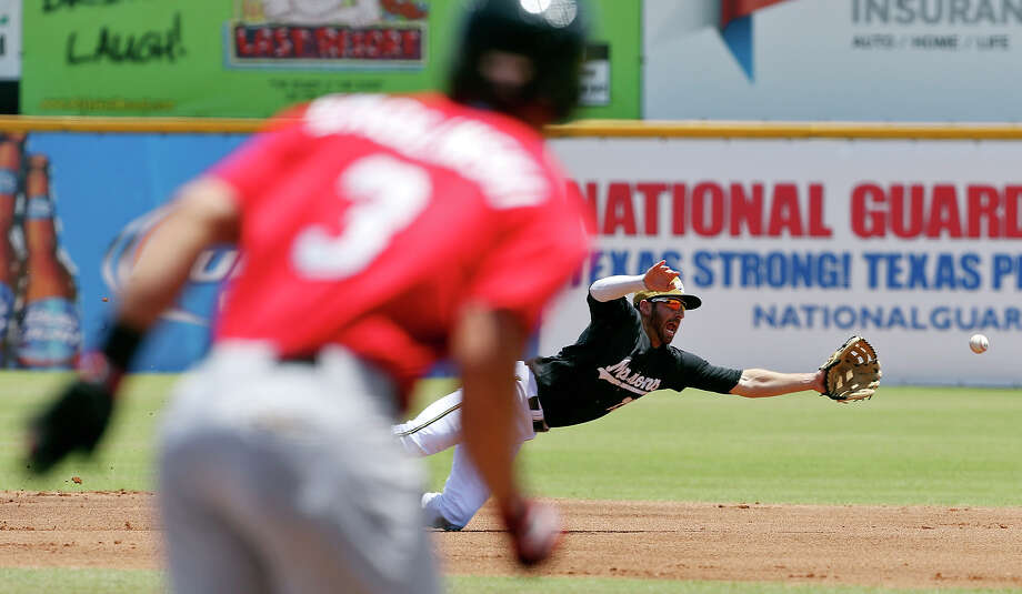 San Antonio Missions' Adam Buschini dives for a hit by Frisco Roughriders' Jake Smolinski Sunday May 18, 2014 at Nelson W. Wolff Municipal Stadium. Smolinski was safe at first. Photo: Edward A. Ornelas, San Antonio Express-News / © 2014 San Antonio Express-News