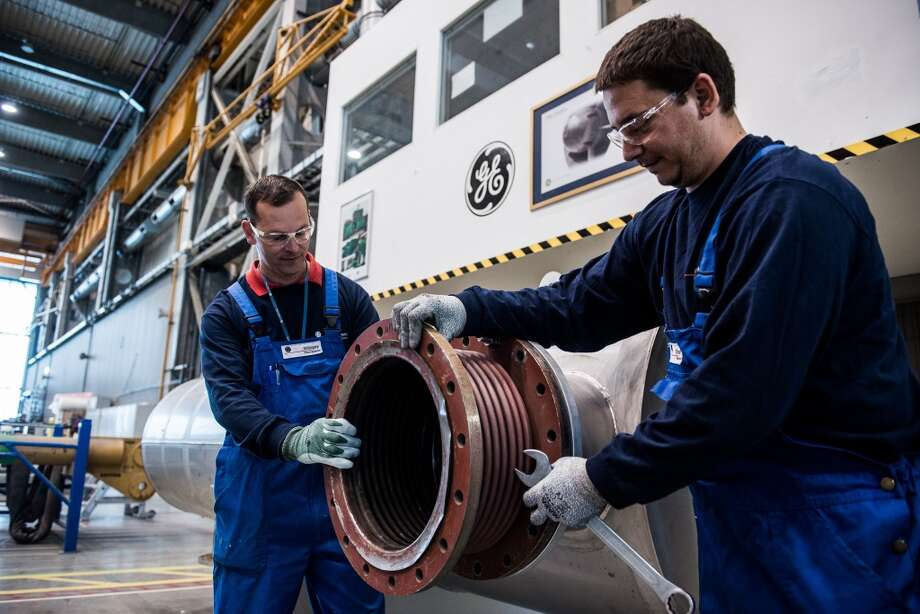 Workers disassemble a pipe used in turbine assembly at the GE Power and Water plant, operated by General Electric Co., in Veresgyhaz, Hungary, on Thursday, May 15, 2014. GE's $17 billion bid for Alstom SA's energy business is in jeopardy after France gave itself the power to block foreign takeovers in industries it deems strategic. Photographer: Akos Stiller/Bloomberg Photo: Akos Stiller, Bloomberg