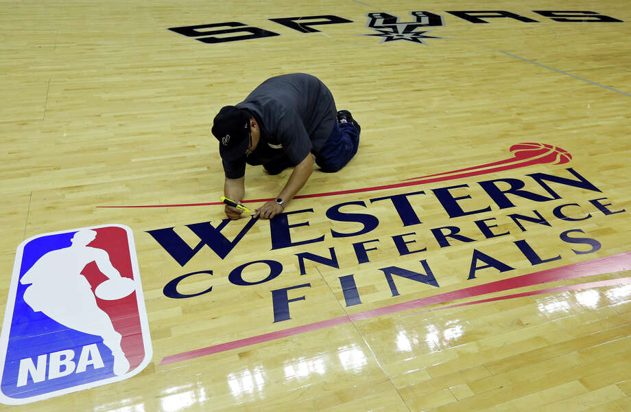 AT&T Center employee Cecilio Santibanez applies the Western Conference Finals logo to the court before Game 1 between the San Antonio Spurs and Oklahoma City Thunder Monday May 19, 2014 at the AT&T Center. Photo: Edward A. Ornelas, San Antonio Express-News / © 2014 San Antonio Express-News