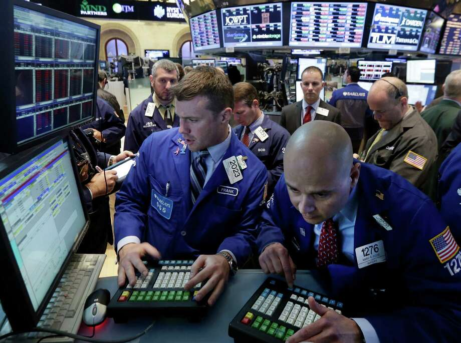 Specialists Frank Masiello, left, and Mario Picone work at the post that handles AT&T on the floor of the New York Stock Exchange Monday, May 19, 2014. Priming itself for the age of Internet-delivered video, AT&T Inc. said it would buy DirecTV for $48.5 billion in cash and stock, or $95 per share. (AP Photo/Richard Drew) ORG XMIT: NYRD109 Photo: Richard Drew / AP