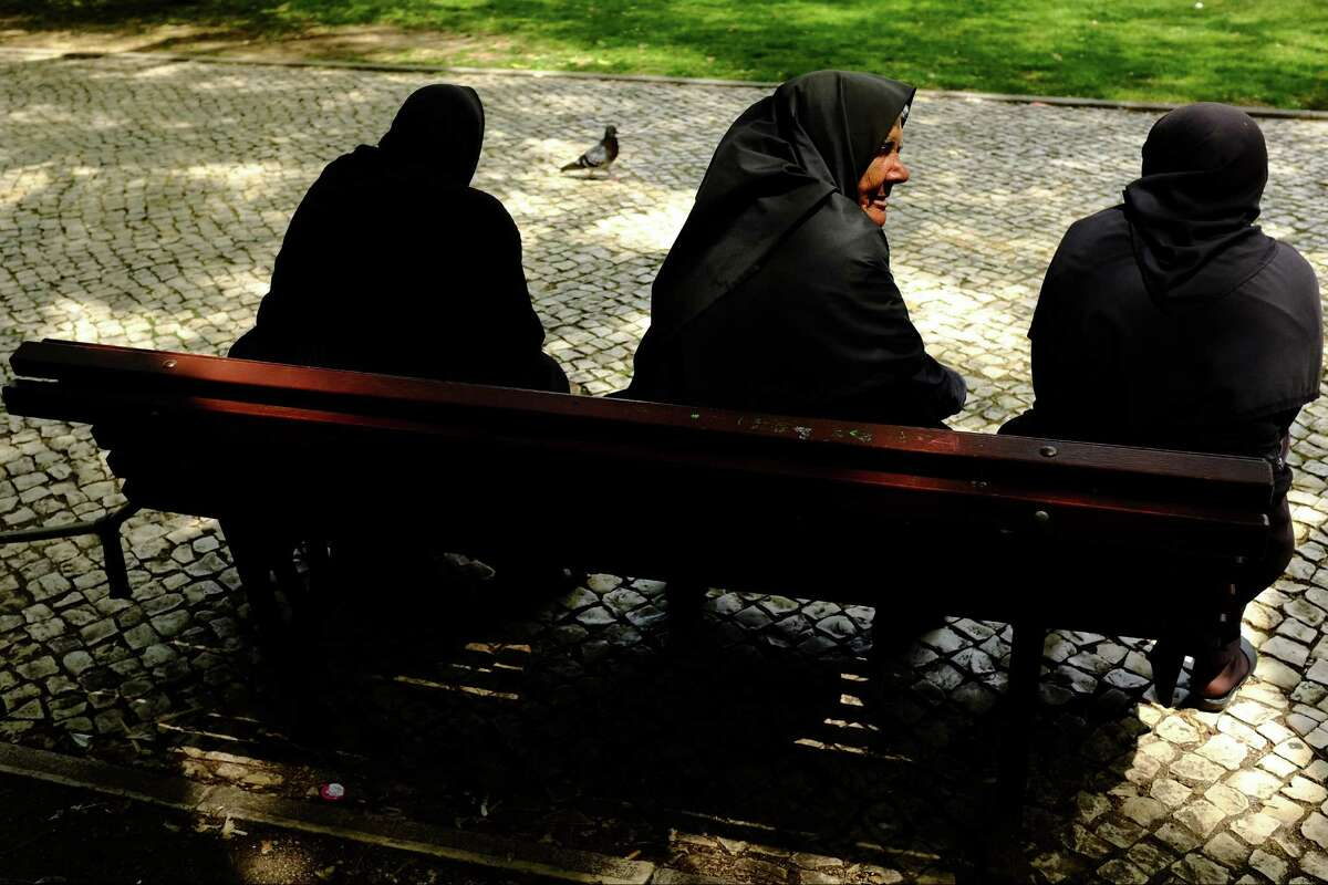 """Self-proclaimed robed """"followers"""" relax on the benches near the Jer-nimos Monastery in May 2014, in Lisbon, Portugal."""