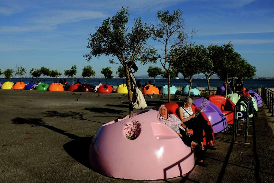 People relax in the colorful plastic blob seats on the waterfront in May 2014, in Lisbon, Portugal. Photo: JORDAN STEAD / JORDAN STEAD