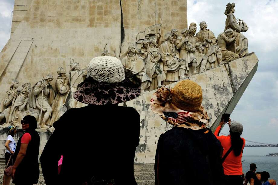 Cameras and hats tilt to view the complexities of the Monument to the Discoveries, a monument on the northern bank of the Tagus River estuary, photographed in May 2014, in Lisbon, Portugal. Photo: JORDAN STEAD / JORDAN STEAD