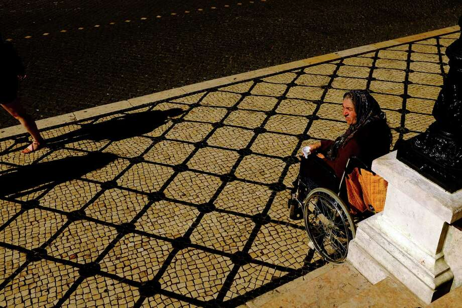 A woman panhandles outside of a church in May 2014, in Lisbon, Portugal. Photo: JORDAN STEAD / JORDAN STEAD