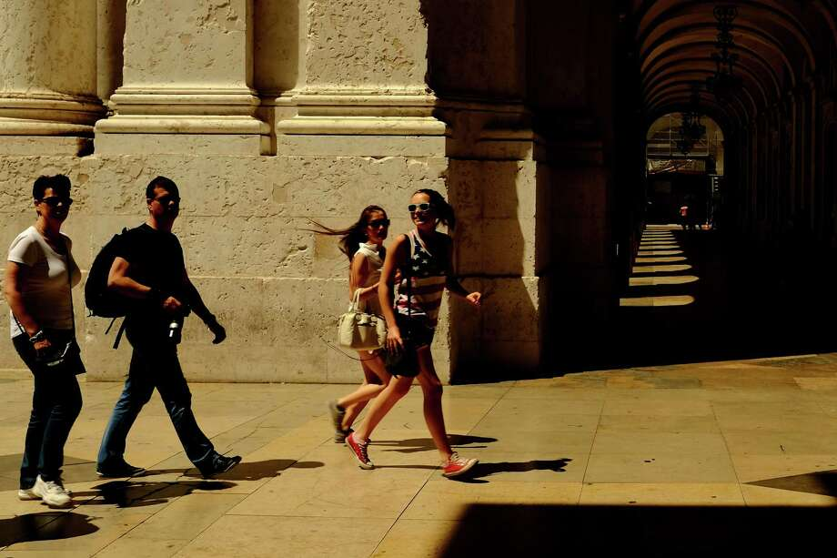Tourists run amongst the arches over a walkway in May 2014, in Lisbon, Portugal. Photo: JORDAN STEAD / JORDAN STEAD