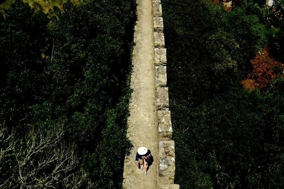 A wide-brimmed tourist navigates the stone pathway on top of a castle wall in May 2014, in Obidos, Portugal. Photo: JORDAN STEAD / JORDAN STEAD