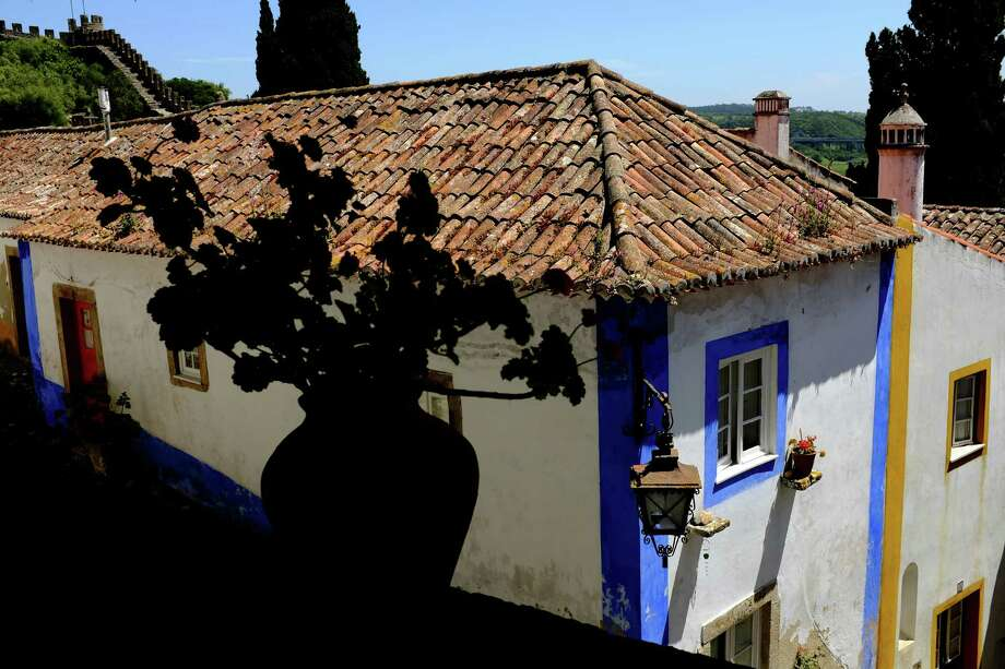 Blue and yellow corner paint adds flair to the outside of homes in May 2014, in Obidos, Portugal. Photo: JORDAN STEAD / JORDAN STEAD