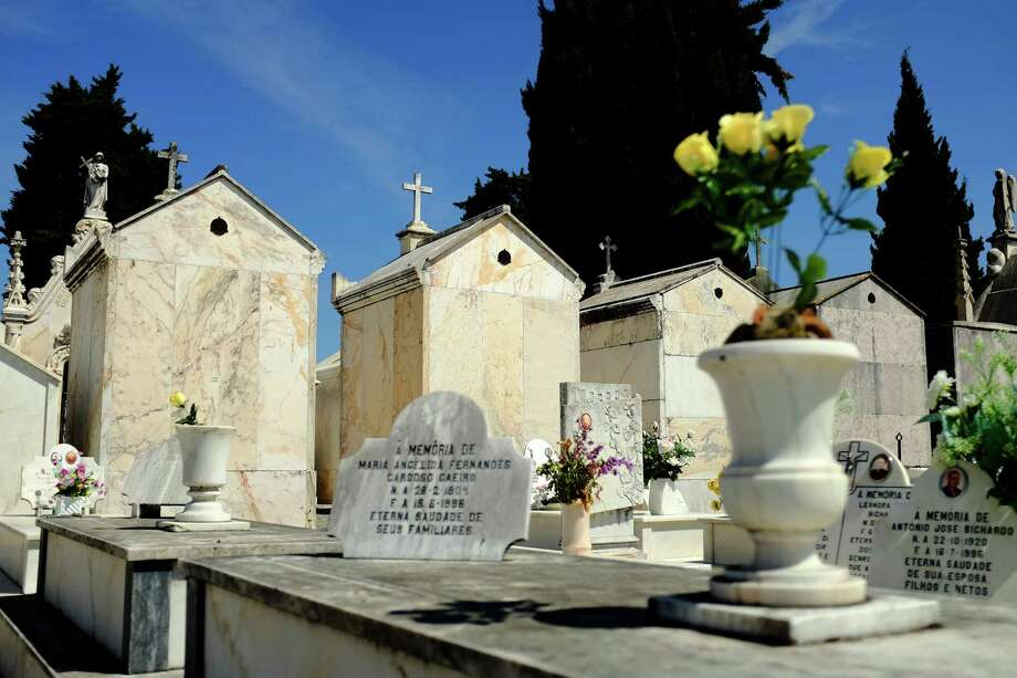Stone gravesides are speckled with text and flowers in May 2014, in Evora, Portugal. Photo: JORDAN STEAD / JORDAN STEAD