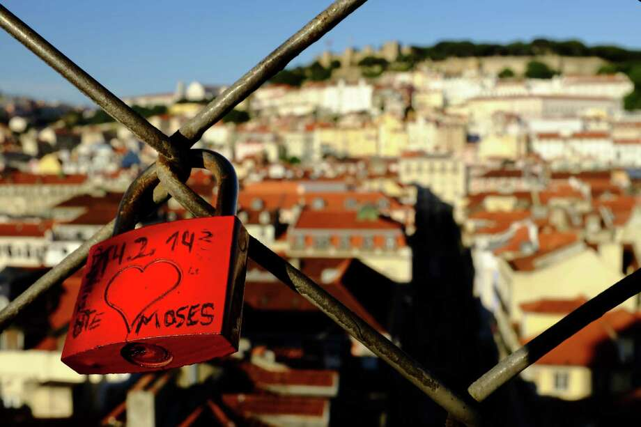 Locks emblazoned with scrawled tourist love hang from a fence in May 2014, in Lisbon, Portugal. Photo: JORDAN STEAD / JORDAN STEAD