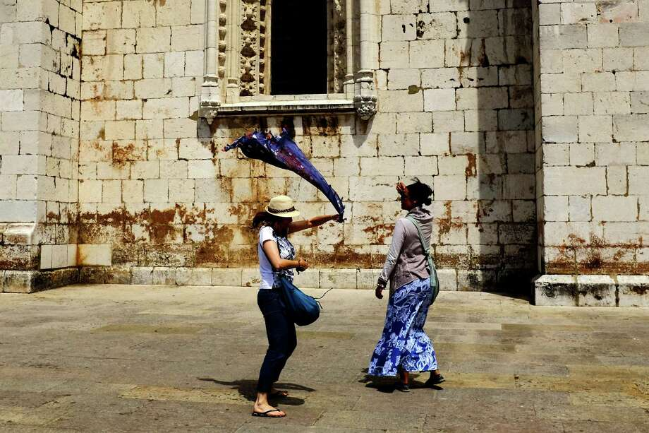 A woman whips her scarf around outside of the Jer—nimos Monastery in May 2014, in Lisbon, Portugal. Photo: JORDAN STEAD / JORDAN STEAD