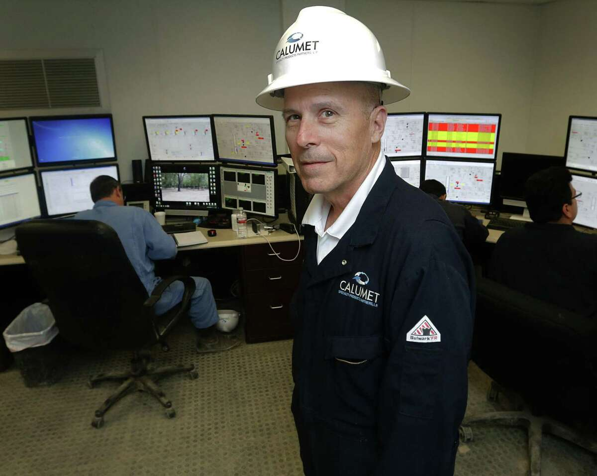 Mike Milam, Plant Manager of Calumet Specialty Products on S. Presa St. talks with visitors in the refinery's control room Friday.
