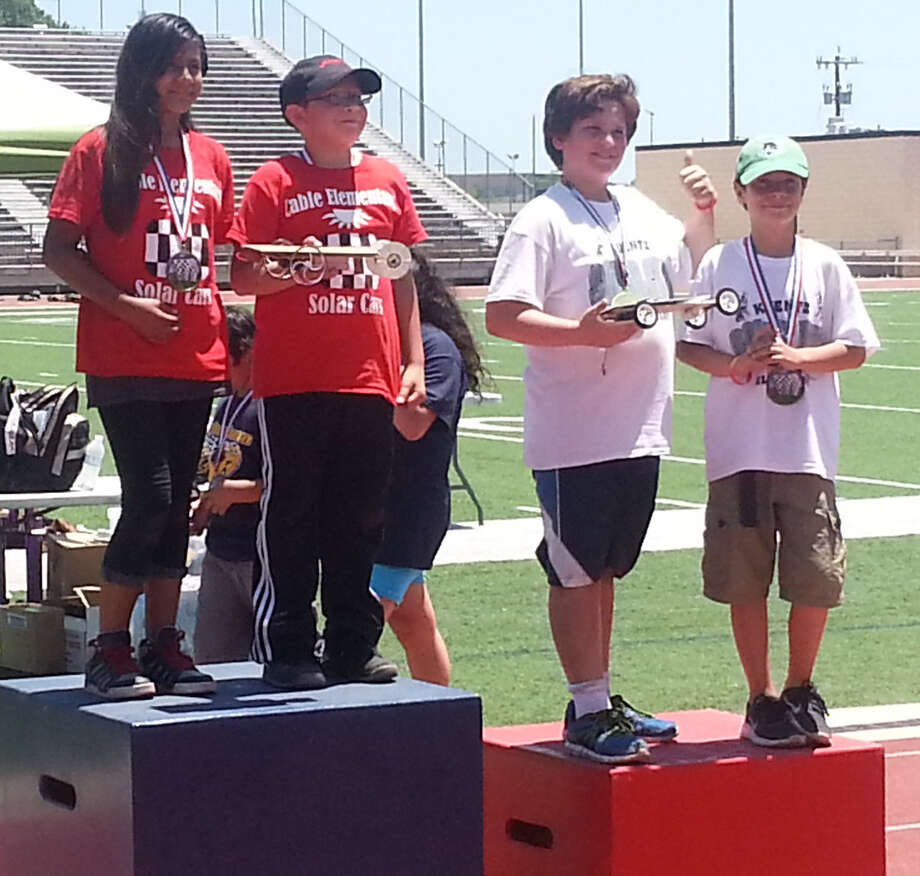 Students from Cable and Kuentz elementary schools take center stage, solar cars in hand, after winning first and second in a heat during the race car contest. Left to right are Cable students Gabriella Badillo and Aidan Muñoz (in red T-shirts) and Kuentz students Jack Boileau and C. J. Vlieger. Photo: Jeremy Gerlach