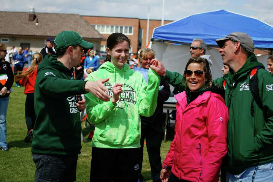 Shenendehowa 8th grader Alexandra Tudor, second from left, reacts to being told by head coach Rob Cloutier, left, that she beat the school record for the 200m with a time of 25.25 seconds during the Lady Eagles Invitational outdoor track meet at Bethlehem High School, Saturday, April 19, 2014 in Delmar, N.Y.   (Dan Little/Special to the Times Union) ORG XMIT: 00026535A Photo: Dan Little / Copyright Dan Little