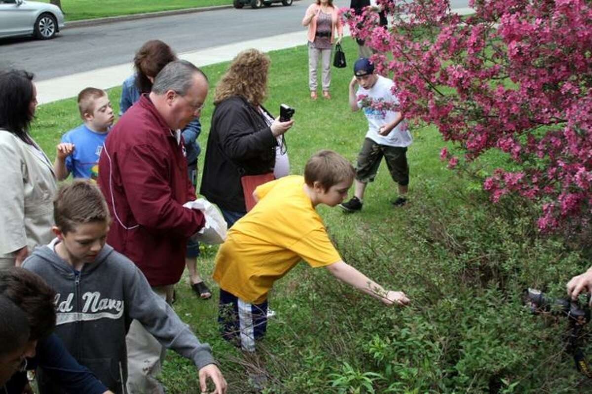 Union College Grounds Manager Tom Heisinger shows students from Pinewood Elementary School how certain insects benefit plants on the college's campus. (Christen Gowan / Union College)