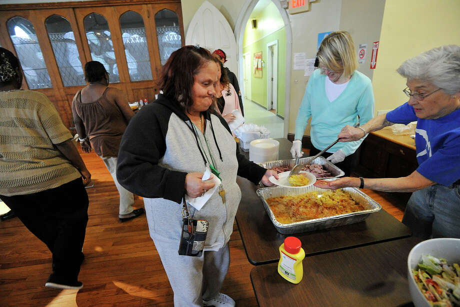 Marilyn Bonilla gets dinner dished up by Helen Dixon, right, a volunteer from Round Hill Community Church of Greenwich, during the free meal program at Inspirica's Woodland Place campus in Stamford, Conn., on Monday, May 19, 2014. According to the recently released Connecticut Coalition to End Homelessness Point-in-Time Count, the Stamford and Greenwich area has seen a 72-percent increase of chronic homelessness among single adults since 2009. The state average is 40-percent. Photo: Jason Rearick / Stamford Advocate