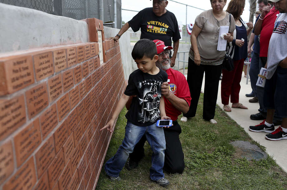 Jeremy Gallardo and his grandfather, Vietnam veteran German Gallardo, Edgewood Class of 1965, view names inscribed on the Veterans Wall of Honor at the 2013 Memorial Day ceremony. Photo: San Antonio Express-News / San Antonio Express-News