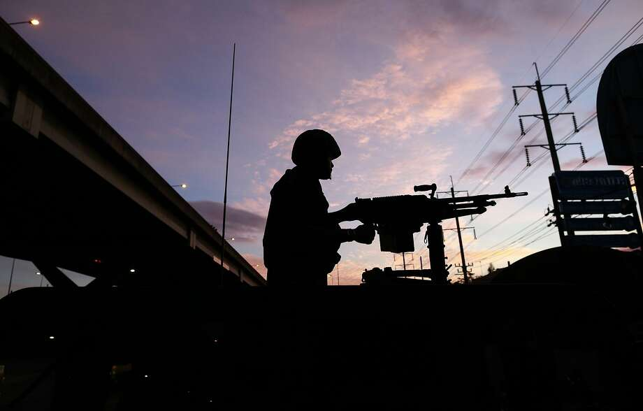 A Thai soldier mans his machine gun atop a military vehicle in Bangkok before dawn on Tuesday. Photo: Wason Wanichakorn, Associated Press
