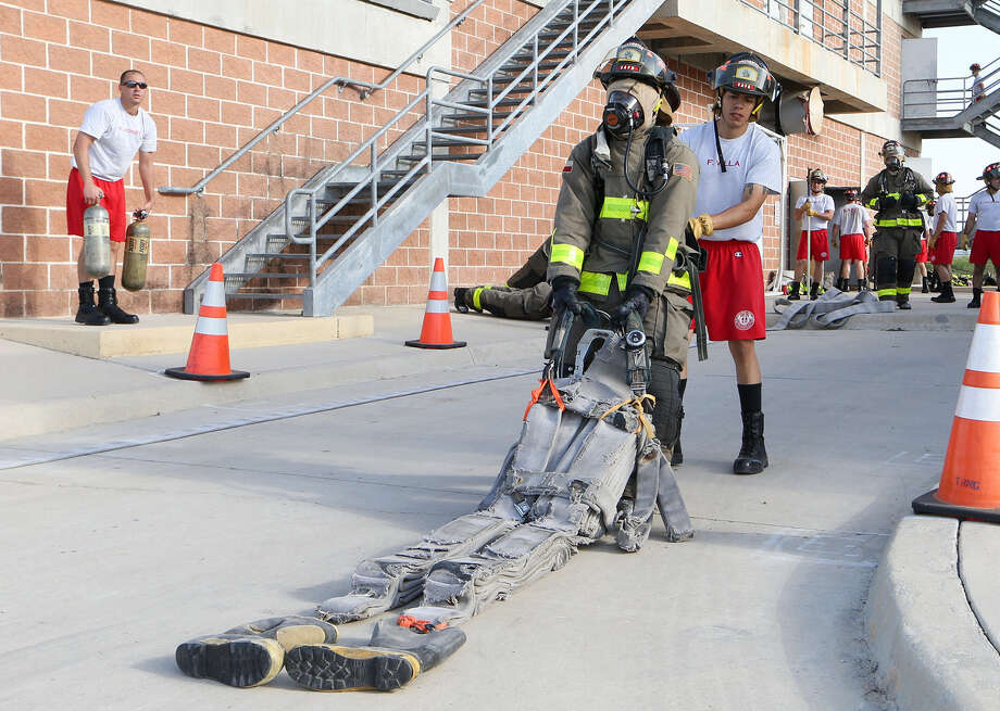 Cadet Guillermo Perez drags a heavy dummy as fellow cadet Fernando Villa spots him from behind during a training exercise at the SAFD Fire Training Academy. Photo: Marvin Pfeiffer / Southside Reporter / Express-News 2014