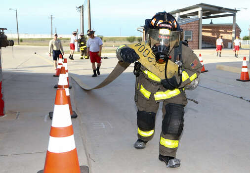 Cadet Juan Avila drags a fire hose during an exercise at the SAFD Fire Training Academy in early May. He is one of just 40 cadets chosen from 3,000 applicants. / Express-News 2014